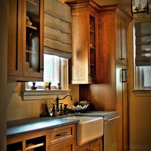 Diseño de cocina lineal, de estilo de casa de campo, con fregadero sobremueble, puertas de armario de madera oscura y electrodomésticos de acero inoxidable