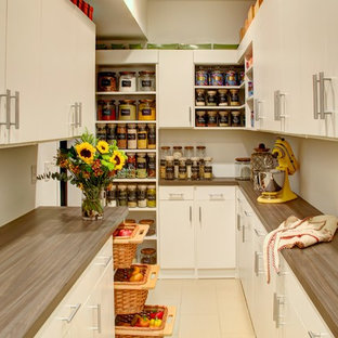 Inspiration for a large country u-shaped kitchen pantry in Philadelphia with flat-panel cabinets, white cabinets, laminate countertops, porcelain flooring and beige floors.