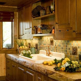 Неиссякаемый источник вдохновения для домашнего уюта: большая линейная, отдельная кухня в стиле кантри с накладной раковиной, фасадами с утопленной филенкой, деревянной столешницей, зеленым фартуком, фартуком из керамической плитки, полом из сланца и техникой под мебельный фасад без острова