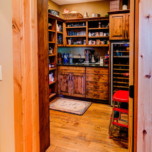 This is an example of a mid-sized country l-shaped kitchen pantry in Minneapolis with medium hardwood floors, brown floor, an undermount sink, raised-panel cabinets, medium wood cabinets, granite benchtops, grey splashback, slate splashback, stainless steel appliances and with island.