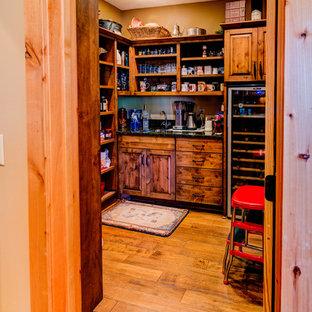 ミネアポリスの中サイズのラスティックスタイルのおしゃれなキッチン (無垢フローリング、茶色い床、アンダーカウンターシンク、レイズドパネル扉のキャビネット、中間色木目調キャビネット、御影石カウンター、グレーのキッチンパネル、スレートのキッチンパネル、シルバーの調理設備) の写真