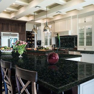 Foto di una grande cucina design con lavello sottopiano, ante bianche, top in granito, paraspruzzi verde, paraspruzzi in lastra di pietra, elettrodomestici bianchi, pavimento in cementine, 2 o più isole e pavimento beige