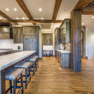 デンバーの大きいラスティックスタイルのおしゃれなキッチン (アンダーカウンターシンク、シェーカースタイル扉のキャビネット、ヴィンテージ仕上げキャビネット、ラミネートカウンター、白いキッチンパネル、モザイクタイルのキッチンパネル、パネルと同色の調理設備、淡色無垢フローリング、茶色い床) の写真