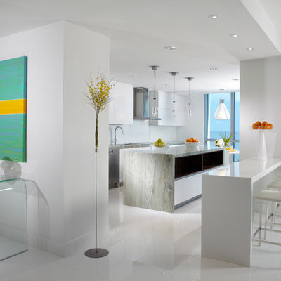 Example of a large trendy galley white floor and marble floor eat-in kitchen design in Miami with a double-bowl sink, white cabinets, marble countertops, white backsplash, glass sheet backsplash, stainless steel appliances, an island, gray countertops and flat-panel cabinets
