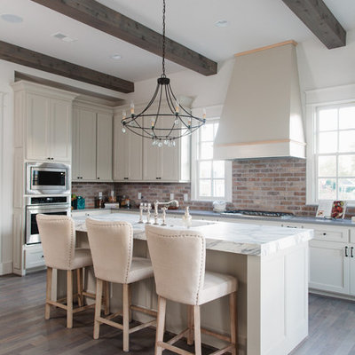 Example of a farmhouse dark wood floor and brown floor kitchen design in Birmingham with shaker cabinets, white cabinets, red backsplash, brick backsplash, black appliances and an island