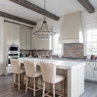 Idéer för lantliga u-kök, med skåp i shakerstil, vita skåp, rött stänkskydd, stänkskydd i tegel, svarta vitvaror, mörkt trägolv, en köksö och brunt golv