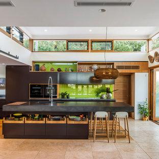 他の地域の中サイズのコンテンポラリースタイルのおしゃれなキッチン (アンダーカウンターシンク、濃色木目調キャビネット、コンクリートカウンター、緑のキッチンパネル、ガラス板のキッチンパネル、シルバーの調理設備の、淡色無垢フローリング、マルチカラーの床、フラットパネル扉のキャビネット) の写真