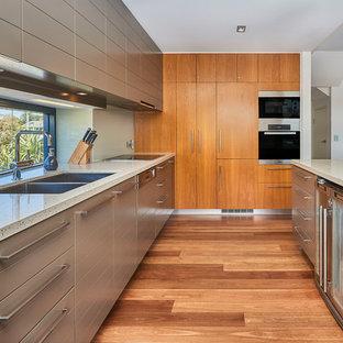 Réalisation d'une cuisine ethnique en L avec un évier encastré, un placard à porte plane, des portes de placard marrons, une crédence en fenêtre, un électroménager en acier inoxydable, un sol en bois clair, un îlot central, un sol marron et un plan de travail beige.