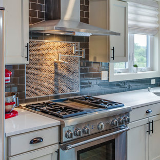 Photo of an arts and crafts l-shaped eat-in kitchen in Grand Rapids with an undermount sink, shaker cabinets, white cabinets, granite benchtops, black splashback, ceramic splashback, stainless steel appliances, laminate floors, with island, brown floor and multi-coloured benchtop.