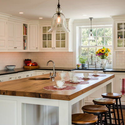 Large country u-shaped medium tone wood floor and brown floor eat-in kitchen photo in Philadelphia with a farmhouse sink, white cabinets, white backsplash, subway tile backsplash, stainless steel appliances, an island, wood countertops, black countertops and beaded inset cabinets