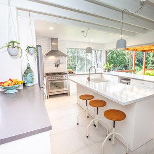 ゴールドコーストの中くらいのエクレクティックスタイルのおしゃれなキッチン (エプロンフロントシンク、シェーカースタイル扉のキャビネット、白いキャビネット、白いキッチンパネル、サブウェイタイルのキッチンパネル、シルバーの調理設備、磁器タイルの床、白い床、マルチカラーのキッチンカウンター) の写真