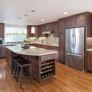This is an example of a large contemporary l-shaped open plan kitchen in San Francisco with a farmhouse sink, shaker cabinets, brown cabinets, granite benchtops, beige splashback, glass tile splashback, stainless steel appliances, medium hardwood floors, with island and brown floor.