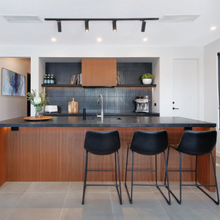 Mid-sized contemporary galley open plan kitchen in Sydney with an undermount sink, flat-panel cabinets, black cabinets, quartz benchtops, black splashback, black appliances, ceramic floors, with island, black benchtop, mosaic tile splashback and grey floor.