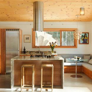 Пример оригинального дизайна: угловая кухня среднего размера в стиле модернизм с обеденным столом, островом, врезной раковиной, техникой из нержавеющей стали, фасадами в стиле шейкер, светлыми деревянными фасадами, столешницей из гранита, серым фартуком, фартуком из каменной плиты, бетонным полом и серым полом