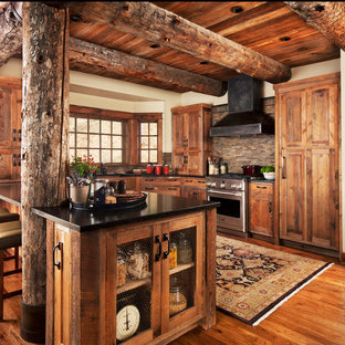 Medium sized rustic u-shaped kitchen in Detroit with shaker cabinets, medium wood cabinets, multi-coloured splashback, matchstick tiled splashback, stainless steel appliances, medium hardwood flooring, a breakfast bar and composite countertops.
