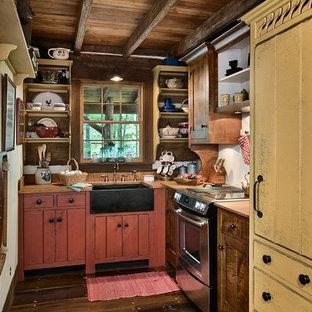 Foto på ett litet rustikt l-kök, med en rustik diskho, röda skåp, integrerade vitvaror och mörkt trägolv