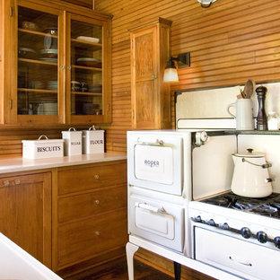 ミネアポリスのシャビーシック調のおしゃれなキッチン (ガラス扉のキャビネット、中間色木目調キャビネット、白い調理設備) の写真