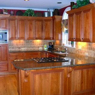 Arts and crafts l-shaped kitchen in Atlanta with louvered cabinets, medium wood cabinets, granite benchtops, beige splashback and ceramic splashback.