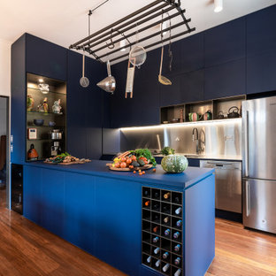 This is an example of a large contemporary u-shaped kitchen in Melbourne with a double-bowl sink, flat-panel cabinets, blue cabinets, solid surface benchtops, grey splashback, metal splashback, stainless steel appliances, medium hardwood floors, a peninsula, brown floor and blue benchtop.