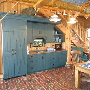 クリーブランドの広いラスティックスタイルのおしゃれなキッチン (ドロップインシンク、インセット扉のキャビネット、青いキャビネット、人工大理石カウンター、ベージュキッチンパネル、石スラブのキッチンパネル、シルバーの調理設備、レンガの床、赤い床) の写真