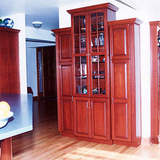 Inspiration for a single-wall kitchen pantry in Other with glass-front cabinets, dark wood cabinets, light hardwood flooring and an island.