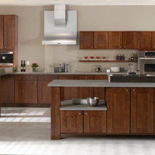 ヒューストンの中サイズのインダストリアルスタイルのおしゃれなアイランドキッチン (シェーカースタイル扉のキャビネット、濃色木目調キャビネット、コンクリートカウンター、シルバーの調理設備の、ドロップインシンク、グレーの床) の写真