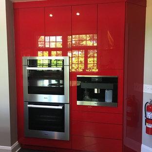 ニューヨークの大きいモダンスタイルのおしゃれなキッチン (アンダーカウンターシンク、フラットパネル扉のキャビネット、赤いキャビネット、クオーツストーンカウンター、赤いキッチンパネル、シルバーの調理設備の、グレーの床) の写真