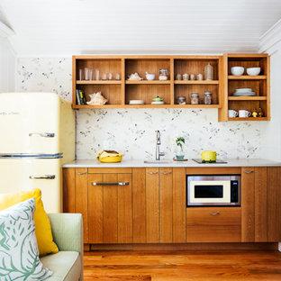 Modelo de cocina lineal, marinera, pequeña, abierta, sin isla, con fregadero bajoencimera, puertas de armario de madera oscura, electrodomésticos de colores, suelo de madera en tonos medios, encimeras blancas y armarios abiertos