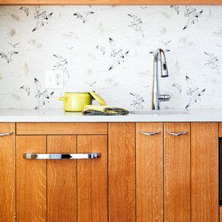 ポートランド(メイン)の小さいビーチスタイルのおしゃれなI型キッチン (アンダーカウンターシンク、フラットパネル扉のキャビネット、中間色木目調キャビネット、カラー調理設備、無垢フローリング、白いキッチンカウンター) の写真