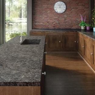 オクラホマシティの中サイズのコンテンポラリースタイルのおしゃれなキッチン (アンダーカウンターシンク、シェーカースタイル扉のキャビネット、中間色木目調キャビネット、珪岩カウンター、ピンクのキッチンパネル、レンガのキッチンパネル、シルバーの調理設備の、無垢フローリング、茶色い床) の写真