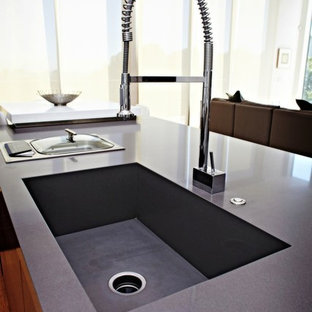 Inspiration for a large contemporary galley open plan kitchen in Seattle with an integrated sink, quartz benchtops, flat-panel cabinets, dark wood cabinets, stainless steel appliances, light hardwood floors, with island, beige floor and grey benchtop.