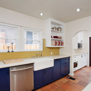 Enclosed kitchen - mid-sized mediterranean galley terra-cotta floor enclosed kitchen idea in Los Angeles with a farmhouse sink, blue cabinets, yellow backsplash, mosaic tile backsplash, shaker cabinets, white appliances and no island