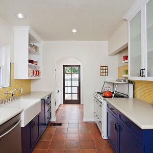 Mid-sized eclectic galley separate kitchen in Los Angeles with a farmhouse sink, shaker cabinets, blue cabinets, yellow splashback, mosaic tile splashback, white appliances, terra-cotta floors, brown floor and no island.