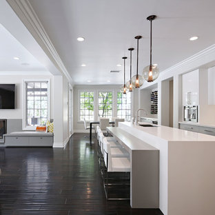 Inspiration for a large contemporary galley open plan kitchen in Los Angeles with flat-panel cabinets, white cabinets, white splashback, stainless steel appliances, an undermount sink, quartz benchtops, porcelain splashback, dark hardwood floors and with island.