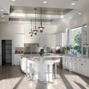 Mittelgroße Moderne Wohnküche in U-Form mit Doppelwaschbecken, profilierten Schrankfronten, weißen Schränken, Granit-Arbeitsplatte, Küchenrückwand in Weiß, Rückwand aus Mosaikfliesen, Küchengeräten aus Edelstahl, braunem Holzboden und Kücheninsel in Los Angeles
