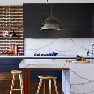 Photo of a contemporary galley eat-in kitchen in Sydney with quartz benchtops, flat-panel cabinets, black cabinets, white splashback, stone slab splashback, medium hardwood floors, with island, brown floor and white benchtop.