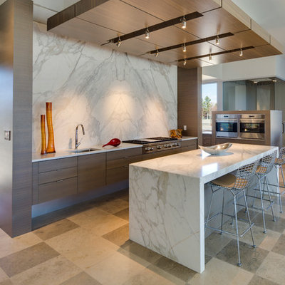 Trendy open concept kitchen photo in Albuquerque with flat-panel cabinets, marble countertops, stone slab backsplash, stainless steel appliances, an undermount sink, dark wood cabinets, white backsplash and an island