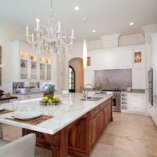 マイアミの広いエクレクティックスタイルのおしゃれなキッチン (アンダーカウンターシンク、シェーカースタイル扉のキャビネット、白いキャビネット、クオーツストーンカウンター、グレーのキッチンパネル、石スラブのキッチンパネル、シルバーの調理設備、トラバーチンの床、ベージュの床) の写真