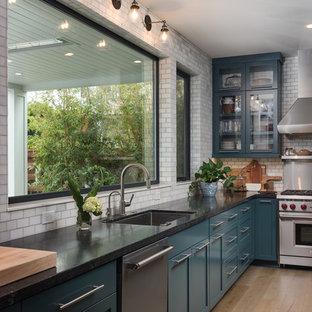 Amerikansk inredning av ett mellanstort kök, med skåp i shakerstil, blå skåp, granitbänkskiva och en halv köksö