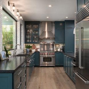 Offene, Zweizeilige, Mittelgroße Klassische Küche mit Schrankfronten im Shaker-Stil, blauen Schränken, Granit-Arbeitsplatte, Halbinsel, Unterbauwaschbecken, Küchenrückwand in Grau, Rückwand aus Metrofliesen, Küchengeräten aus Edelstahl, braunem Holzboden und braunem Boden in San Diego