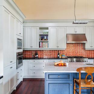 Стильный дизайн: кухня в классическом стиле с фасадами с утопленной филенкой, оранжевым фартуком, техникой из нержавеющей стали и синими фасадами - последний тренд