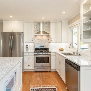 カルガリーの小さいトランジショナルスタイルのおしゃれなキッチン (アンダーカウンターシンク、シェーカースタイル扉のキャビネット、白いキャビネット、白いキッチンパネル、シルバーの調理設備の、御影石カウンター、モザイクタイルのキッチンパネル、淡色無垢フローリング、茶色い床) の写真
