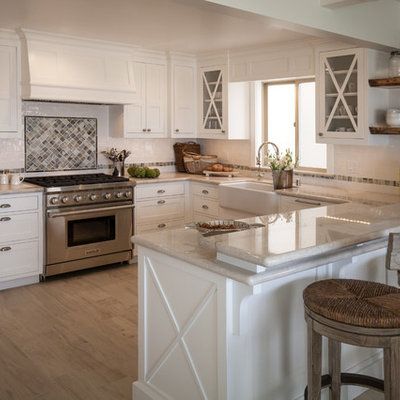 Kitchen - mid-sized coastal u-shaped kitchen idea in Los Angeles with a farmhouse sink, shaker cabinets, white cabinets, quartzite countertops, stainless steel appliances and a peninsula