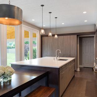 Esempio di una cucina design di medie dimensioni con lavello sottopiano, ante lisce, ante marroni, parquet scuro, isola, elettrodomestici da incasso, top in laminato, paraspruzzi grigio, paraspruzzi con lastra di vetro e pavimento marrone