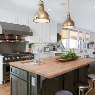 Inspiration for a beach style l-shaped open concept kitchen remodel in Orange County with a farmhouse sink, white cabinets, wood countertops, white backsplash and stainless steel appliances