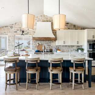 На фото: п-образная кухня в стиле кантри с фасадами в стиле шейкер, белыми фасадами, фартуком из каменной плитки, техникой из нержавеющей стали, светлым паркетным полом, островом, белой столешницей и сводчатым потолком с