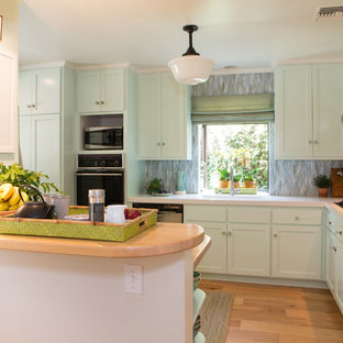 Mid-sized beach style enclosed kitchen ideas - Mid-sized coastal l-shaped medium tone wood floor enclosed kitchen photo in Los Angeles with a peninsula, shaker cabinets, green cabinets, solid surface countertops, green backsplash, glass sheet backsplash, stainless steel appliances and a single-bowl sink