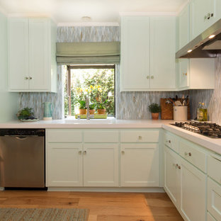 Inspiration for a mid-sized beach style l-shaped medium tone wood floor enclosed kitchen remodel in Los Angeles with a peninsula, shaker cabinets, green cabinets, solid surface countertops, green backsplash, glass sheet backsplash, stainless steel appliances and a single-bowl sink