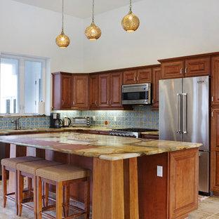 ロサンゼルスの中サイズの地中海スタイルのおしゃれなキッチン (青いキッチンパネル、アンダーカウンターシンク、レイズドパネル扉のキャビネット、中間色木目調キャビネット、オニキスカウンター、シルバーの調理設備、セラミックタイルの床) の写真