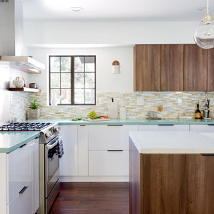 Midcentury l-shaped kitchen in Los Angeles with a farmhouse sink, flat-panel cabinets, dark wood cabinets, multi-coloured splashback, matchstick tile splashback, panelled appliances, dark hardwood floors, with island, brown floor and green benchtop.
